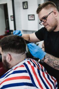 Larion ollóval vágja a vendégünk haját